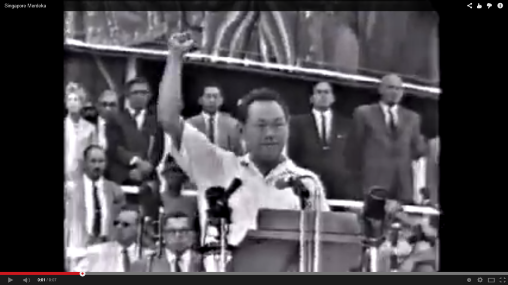 1963, Singapore joins Malaysia: Lee Kuan Yew proclaims Merdeka! from the steps of the City Hall, echoed by a large assembled crowd at the Padang.