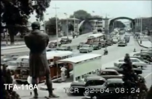 Singapore in 1957: Vehicular traffic crossing Anderson Bridge in front of Victoria Memorial Hall's statue of Sir Thomas Stamford Raffles